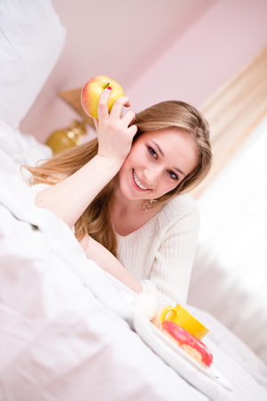 coquete: Young happy smiling coquette  girl in lingerie eating apple lying on her belly in bedroom