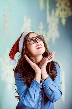 chin on hands: Beautiful teenage girl wearing Santa hat and glasses daydreaming with her hands under her chin on bokeh background looking up copyspace