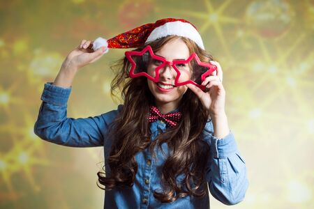 star shaped: Funny happy  teenage girl in Santa hat and star shaped glasses close-up on pastel bokeh background