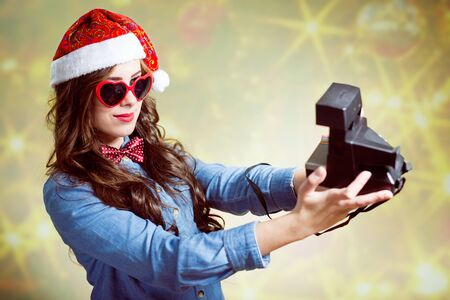 christmas hat: A teenage girl wearing Christmas hat and heart-shaped glasses making selfi with retro camera on bokeh background copyspace Stock Photo