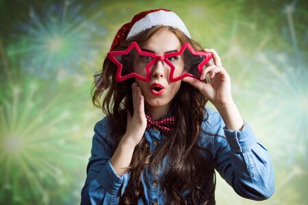 star shaped: Funny surprised teenage girl in Santa hat and star shaped glasses close-up on green bokeh background
