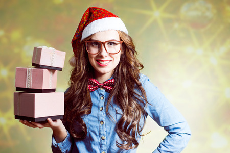 Content smiling young brunette female in Christmas hat and glasses holding  three present boxes on her hand on pastel bokeh background Imagens