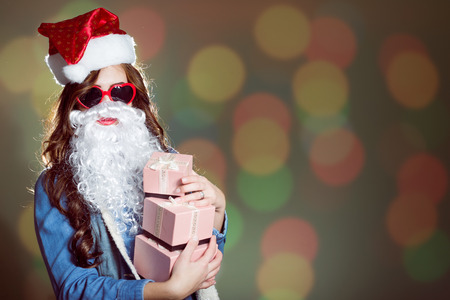 female christmas: Funny young brunette female in Christmas hat and heart shaped sunglasses with three present boxes in her hands on bokeh background copyspace