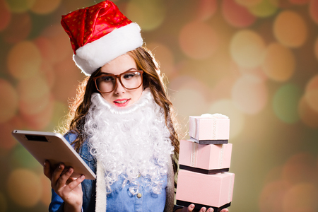 female christmas: Funny young brunette female in Christmas hat and glasses with three present boxes and tablet PC  in her hands on bokeh background copyspace