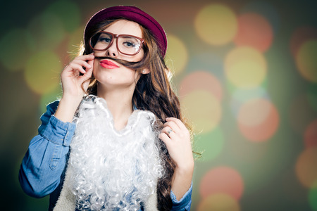 female christmas: Funny young brunette female in Christmas hat, glasses and false beard playing with her hear pretending to have mustache posing on bokeh background copyspace Stock Photo