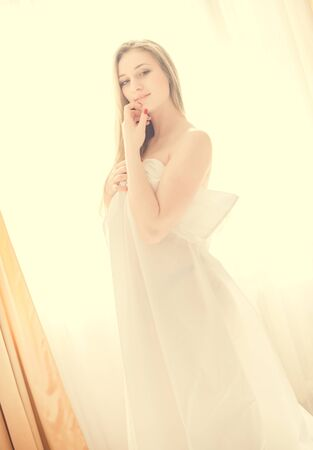 sexi: Vintage picture of sexi young pretty lady in white standing by window on white background Stock Photo