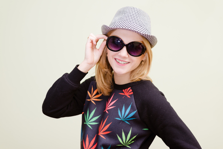 rasta hat: Isolated studio picture of smiling teenage hipster in funny outfit talking on cellphone smiling Stock Photo