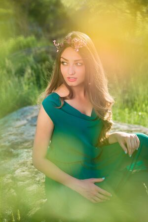 geen: Pretty lady in green dress and flowers in her long hair sunlit sitting on geen meadow Stock Photo