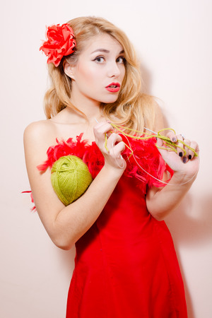barrette: Knitting girl in red dress with flower barrette and feather boa. Stock Photo