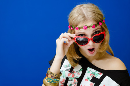 mouth opened: Portrait of surprised hipster woman in sunglasses with her mouth opened. Pretty lady in black shirt touching her sunglasses over deep blue background