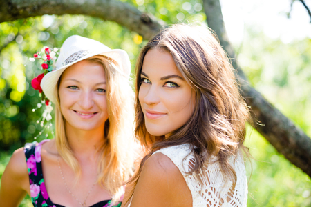 upper half: Closeup portrait of blonde and brunette women who are smiling in sunny summer park. Stock Photo