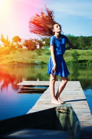 flying hair: Young beautiful lady with flying hair standing on wooden bridge on sunny day