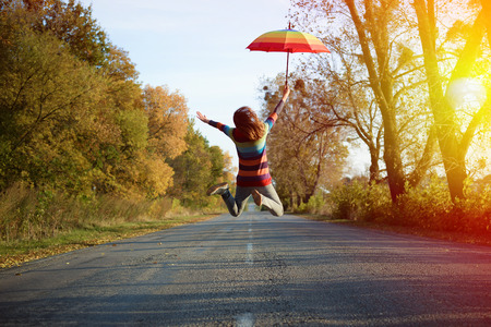 Conceptual picture of jumping lady holding umbrella with arms sideways on empty country road in autumn
