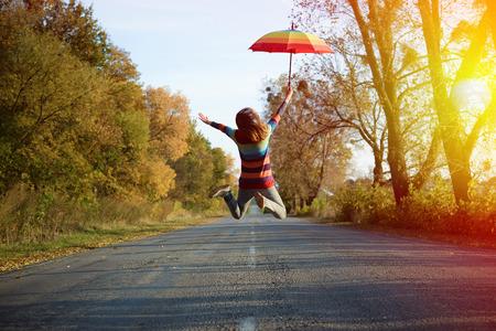 Konzeptionelles Bild der springenden Dame, die Regenschirm mit Armen seitwärts auf leerer Landstraße im Herbst hält