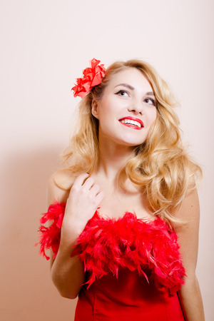 upper half: Surprised blond girl in red dress with flower barrette and feather boa