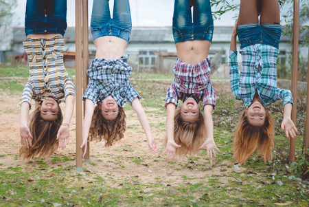 wearing: Four young funny teenage girls in chequered shirts hanging upside down having fun together outdoors
