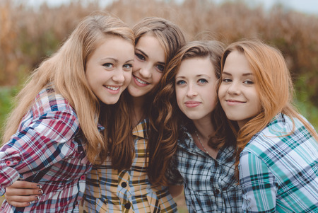 brunette girl: Four happy smiling amazing teenage girls having fun together looking at camera close up picture Stock Photo