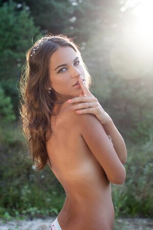 cuerpos desnudos: Joven y bella mujer sensual posando en topless cubriendo sus senos con el dedo en los labios se cierran para arriba