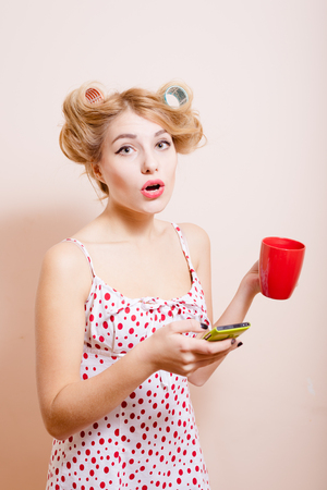 sexi: Isolated close up picture of surprized  sexi pin up lady in curlers holding cup and trying to use her mobile phone