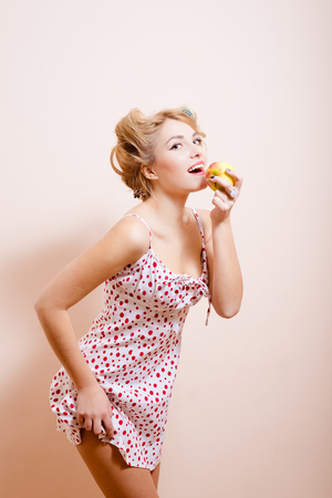 sexi: Copyspace picture of young sexi blonde lady in curlers eating apple and posing showing off her butt