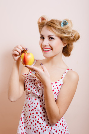 sexi: Young beautiful sexi pin up lady in curlers holding big red apple with both hands smiling happily close up