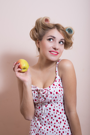 big apple: Half-length portrait of funny amazed pin up girl in curlers holding big apple looking up close up