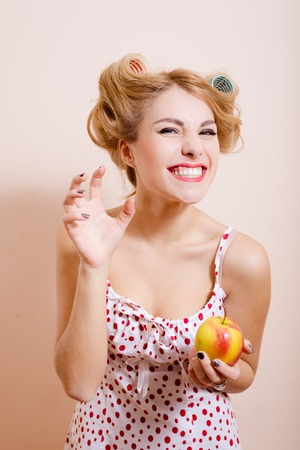 sexi: Isolated close up portrait of excited happy sexi young lady in lingerie and curlers holding apple laughing