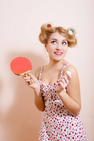 half ball: Half length picture of surprised beautiful pinup female in curlers with tennis racket and ball