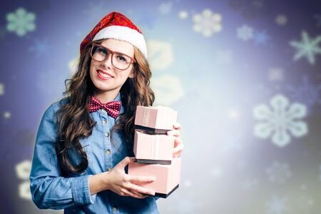 Happy hipster girl in super size eyeglasses wearing xmas santa hat holding three boxes of presents in her hands over purple copy space bokeh background Imagens