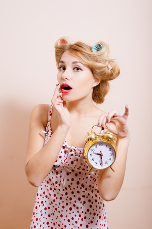 hait: Surprised housewife holding alarm-clock in her hand. Blond woman with hait curlers on opened her mouth with red lips isolated on cream background.