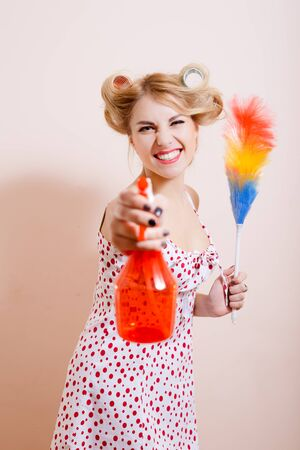 tidying up: Tidying up concept. Happy housewife big smiling with spray and dust cleaner in her hands. Blond woman ready to tide her house. Stock Photo