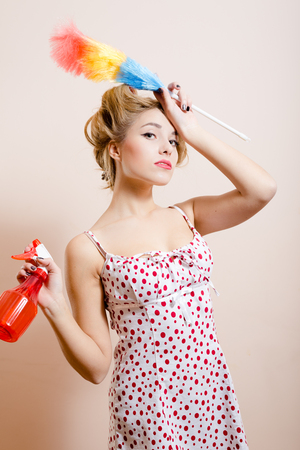 hair curlers: Desperate housewife looking exhausted after cleaning up the house. Tired woman with hair curlers on posing with spray and dust cleaner in her hands.