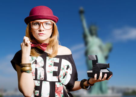 joyfull: Picture of young woman in hipster glasses and hat with . Pretty girl in polka dot bowtie on New York blurred background. Stock Photo