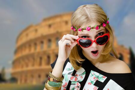 fancy girl: Portrait of excited woman in flower wreath and heart shaped glasses. Fancy girl shocked on Coliseum blurred background. Stock Photo