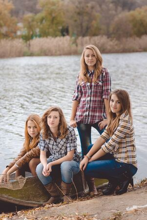 Portrait of four young women beside river in autumn. Pretty girls in jeans smiling at camera on fall countryside background.