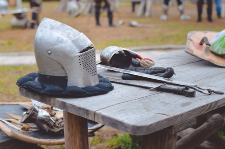medieval blacksmith: Picture of medieval armors on wooden table in countryside. Old metal helmet, swords and gloves waiting for knight on outdoor background.