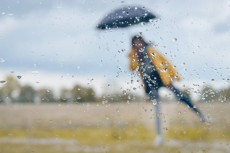 Picture of rainy autumn day. Woman standing under black umbrella with rain drops on window glass foreground.