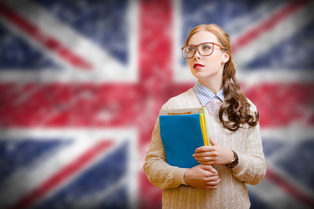 Picture of young woman in glasses and sweater holding files. Student girl on english union jack blurred background Archivio Fotografico