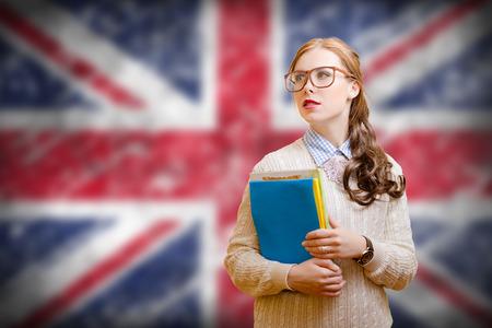 Photo de jeune femme dans des verres et des fichiers de chandail de maintien. Student girl sur l'union Anglais jack floue fond Banque d'images
