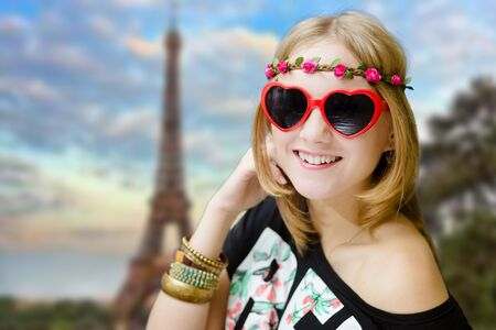 hair band: Portrait of funky woman in flower hair band and ethnic bangles. Pretty girl in heart shaped sunglasses on blurred Eiffel tower background.