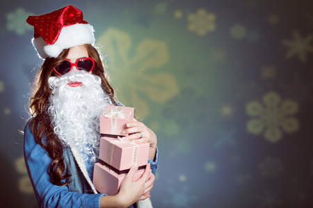 Funny hipster girl in super size heart shaped sunglasses wearing xmas santa hat and false beard, holding three boxes of presents over blue and yellow bokeh copy space background Stockfoto