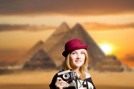 chephren: Picture of joyfull woman in hipster glasses and pot hat with vintage camera. Young traveler smiling on Egypt pyramid blurred background. Stock Photo