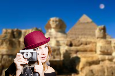 joyfull: Picture of joyfull woman in hipster glasses and pot hat with vintage camera. Young traveler smiling on Egypt pyramid blurred background. Stock Photo