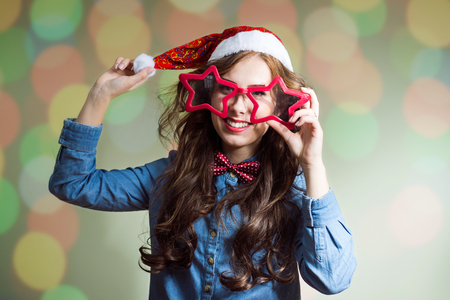 star shaped: Happy funny hipster beautiful young lady in super size star shaped glasses wearing xmas santa hat over olive copy space background