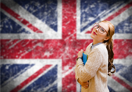 english girl: Picture of young woman in glasses and sweater holding files. Student girl on english union jack blurred background Stock Photo