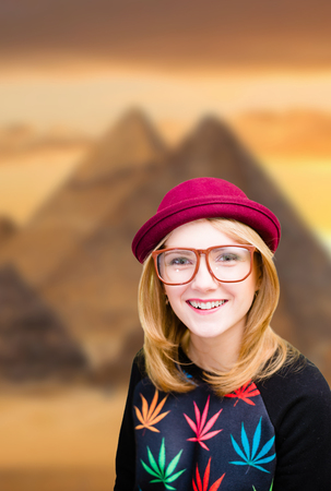 beautiful blonde woman: Picture of joyful woman in hipster glasses and pot hat. Young traveler smiling on Egypt pyramid blurred background.