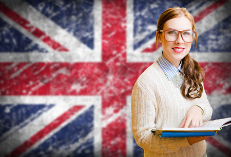 Picture of young woman in glasses and sweater holding files. Student girl on english union jack blurred background Standard-Bild