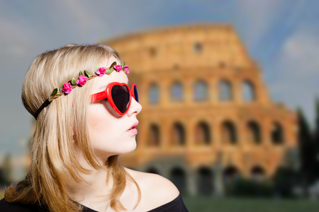 fancy girl: Portrait of young beautiful woman in charming flower wreath and heart shape sunglasses. Fancy girl in glasses on Coliseum blurred background.