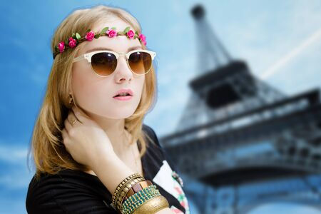 hair band: Portrait of funky woman in flower hair band and ethnic bangles. Pretty girl in sunglasses on blurred Eiffel tower background.