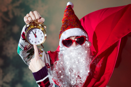 forthcoming: Picture of funny Santa Claus with alarm clock wearing heart shape sunglasses on bright festive bokeh background